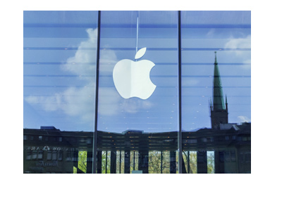 Apple logo in the all glass window.  City skyline reflection in the background.