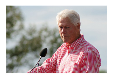 Former president Bill Clinton during an outdoor speach - Wearing a red and white checkered shirt - Year 2014