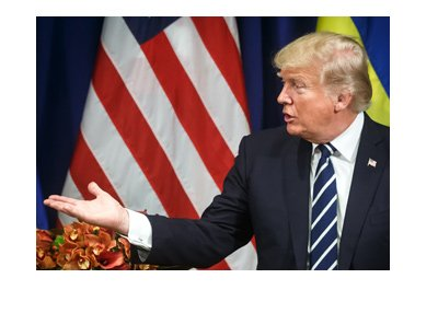 President of United States, Donald Trump, expressing himself in words and with a hand gesture in front of flags of United States and Ukraine.