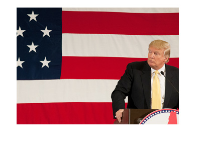 Donald Trump is standing at the podium with the american flag in the background.  He has a look of concern on his face.
