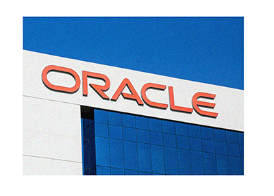 The Oracle company logo on top of a building.  The sky behind is clear.