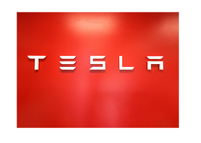 Tesla logo in a showroom.  Red background.  The year is 2018.