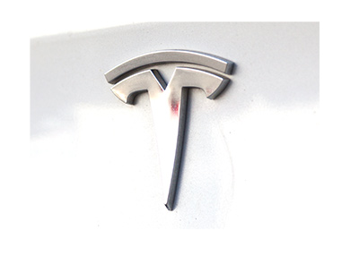 The Tesla logo as it was in the year 2018 on the back of a white car.  Zoomed in.
