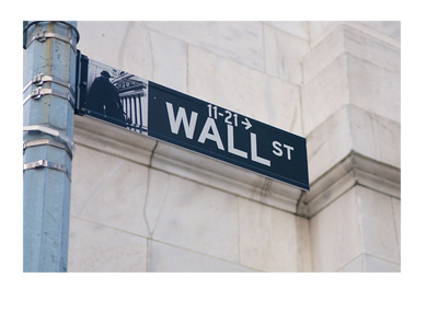 New York - Wall Street street sign in front of a white building wall